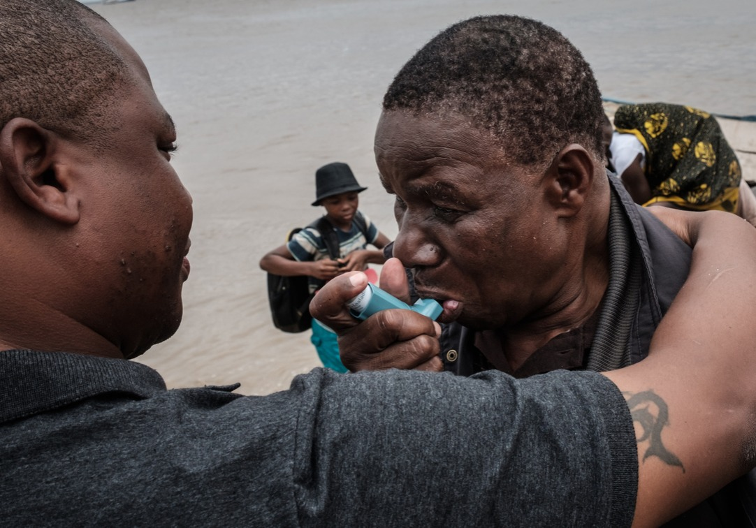 Manuel Machacawa Maezane (R), 76, takes an asthma puffer as he meets his son Aristides (L)