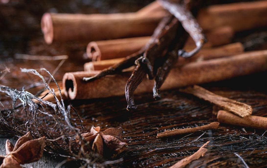 Heap of spices cinnamon sticks, vanilla sticks and anise stars over dark palm crust. Cinnamon health benefits lower blood sugar