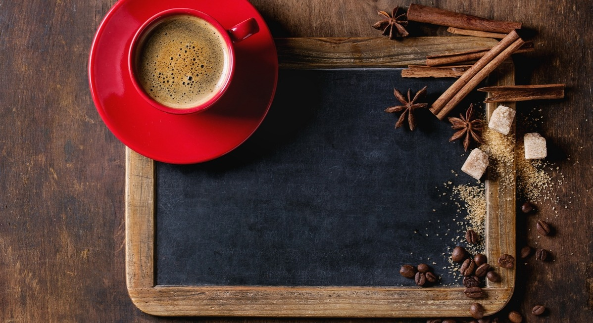 Empty vintage chalkboard, coffee beans, spices, brown sugar and red cup of black coffee over old wooden background. Top view with space for text.