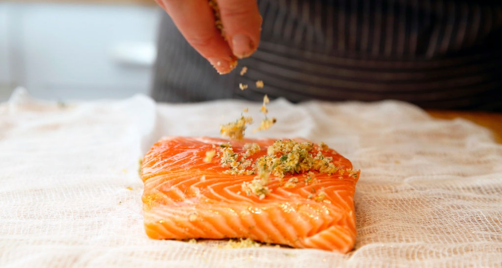 raw salmon being seasoned