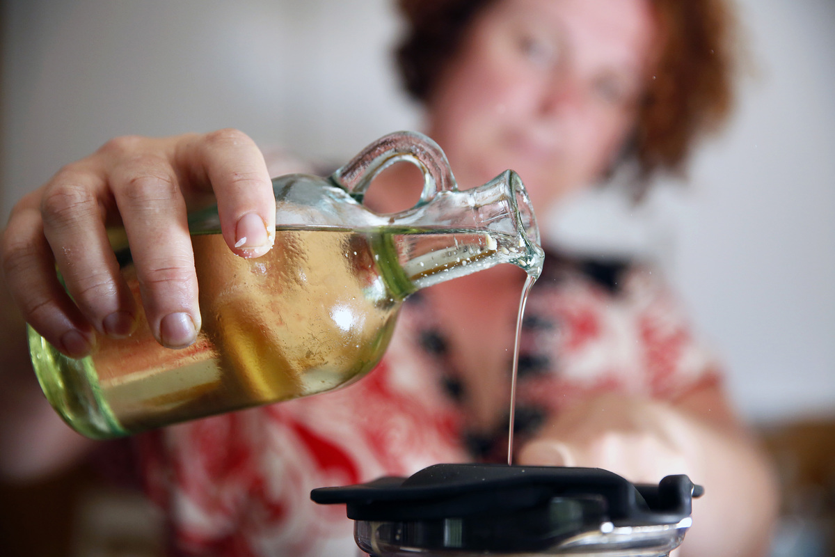 Woman drizzles olive oil into a blender to make spicy aioli.