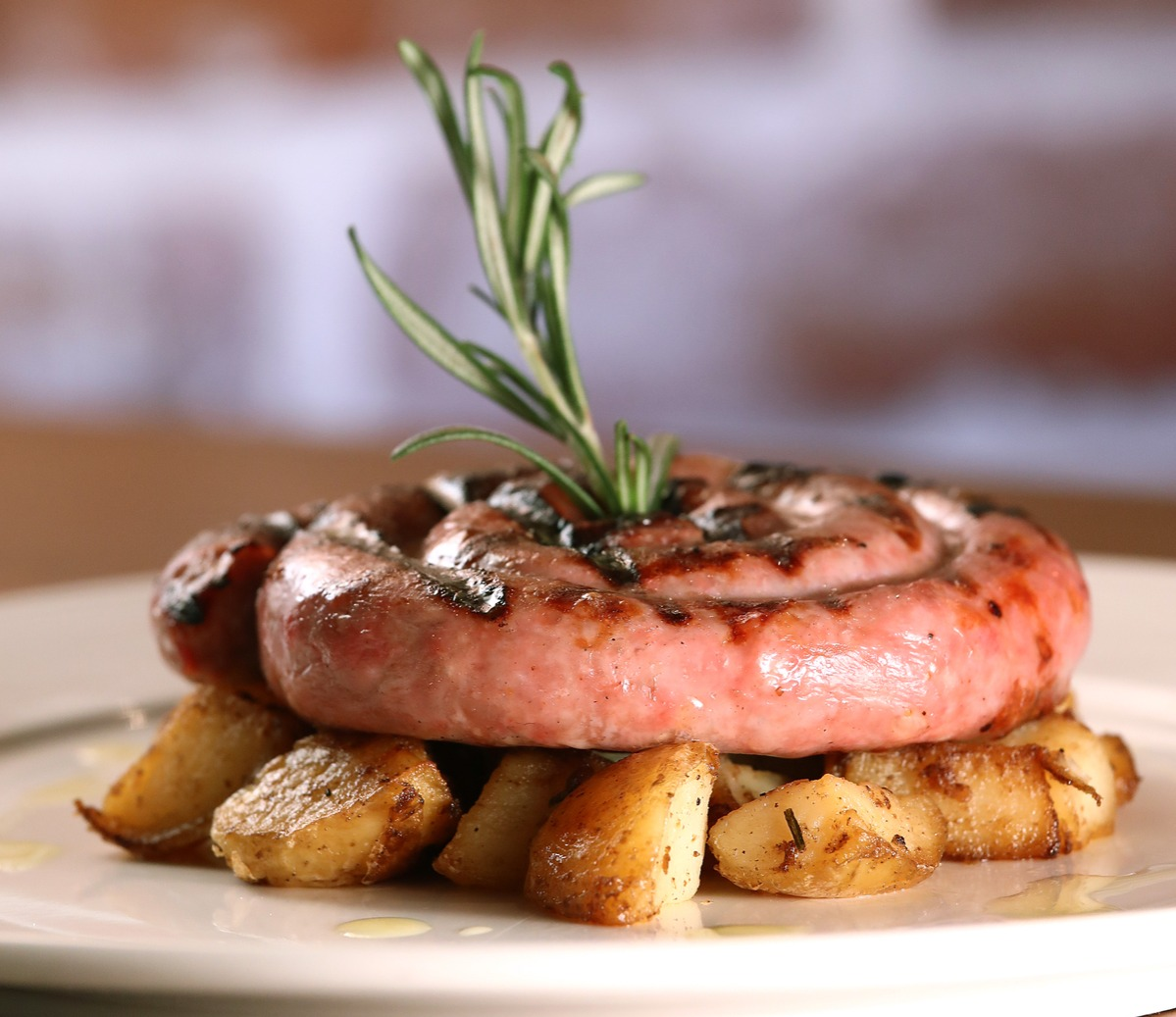Italian sausage and potatoes dish with a rosemary garnish.