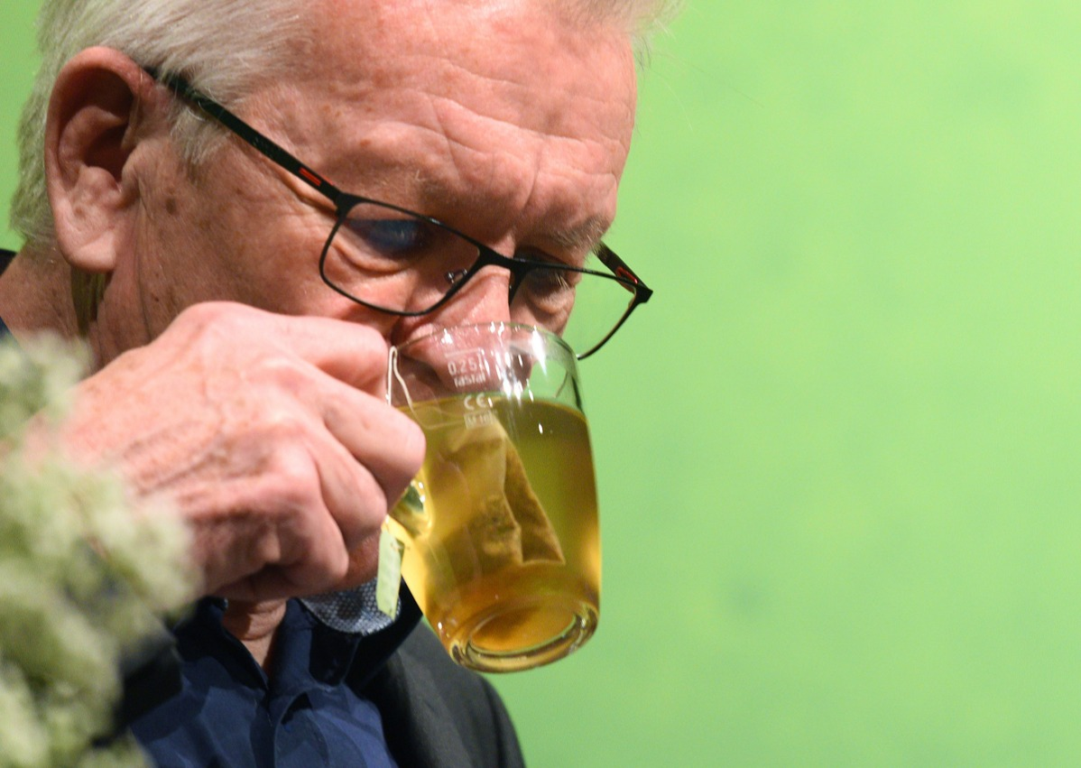 Prime Minister of Baden-Württemberg, drinks from a tea glass during his speech