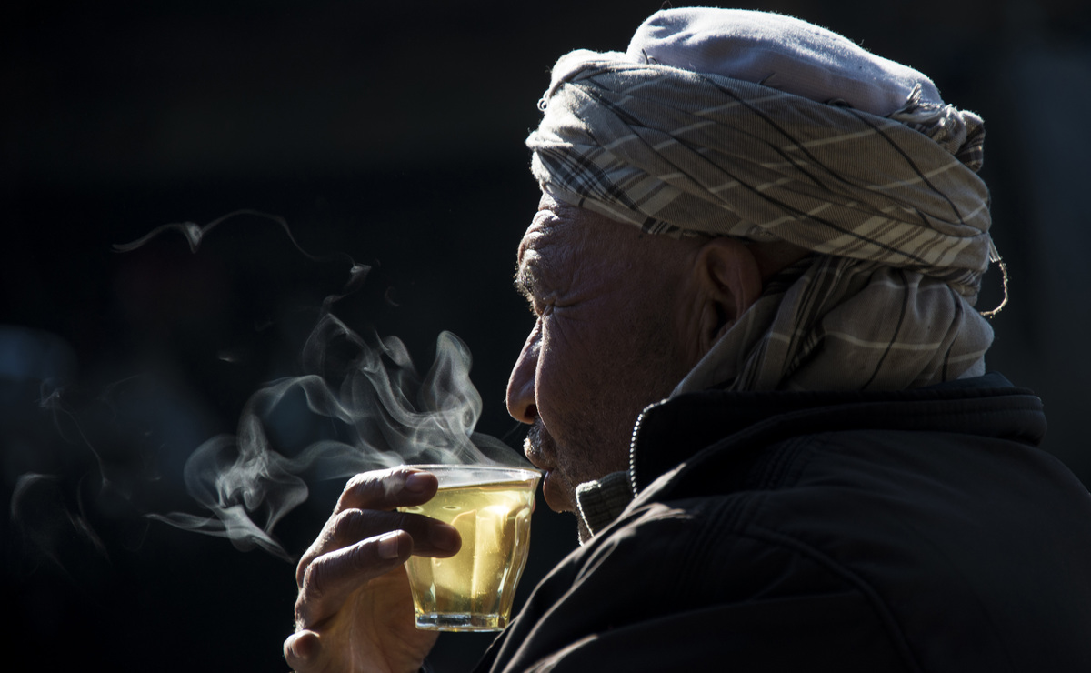 An Afghan man drinks a glass of tea at a second hand vehicle parts shop.
