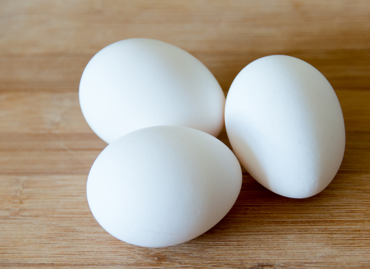 Three white eggs over a wooden surface or cutting board in a kitchen.