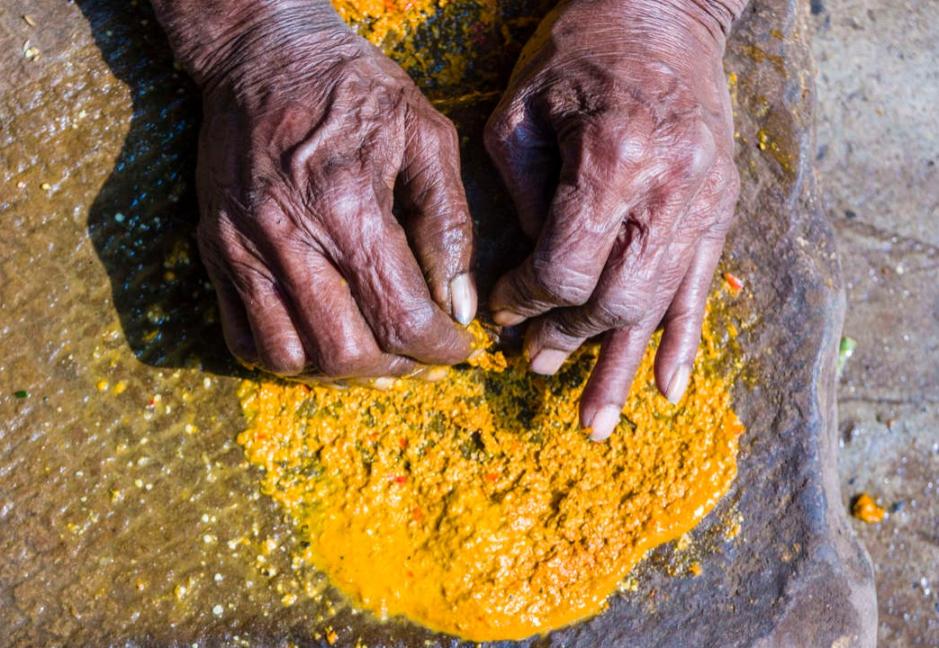 Hands of a woman, grinding turmeric.