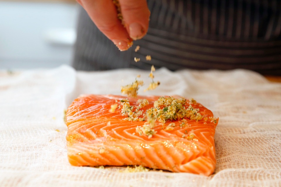 Person sprinkles a citrus rub on a filet of salmon to make gravlax.