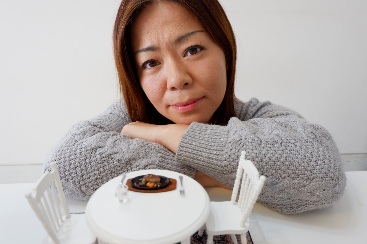 Photographer and YouTuber Yukiko Hasada with one of her tiny dishes on a miniature table