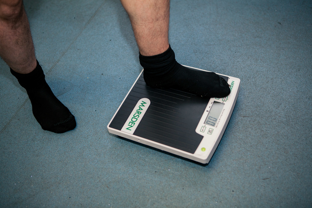 Close up of MAN V FAT football player stepping on the scales