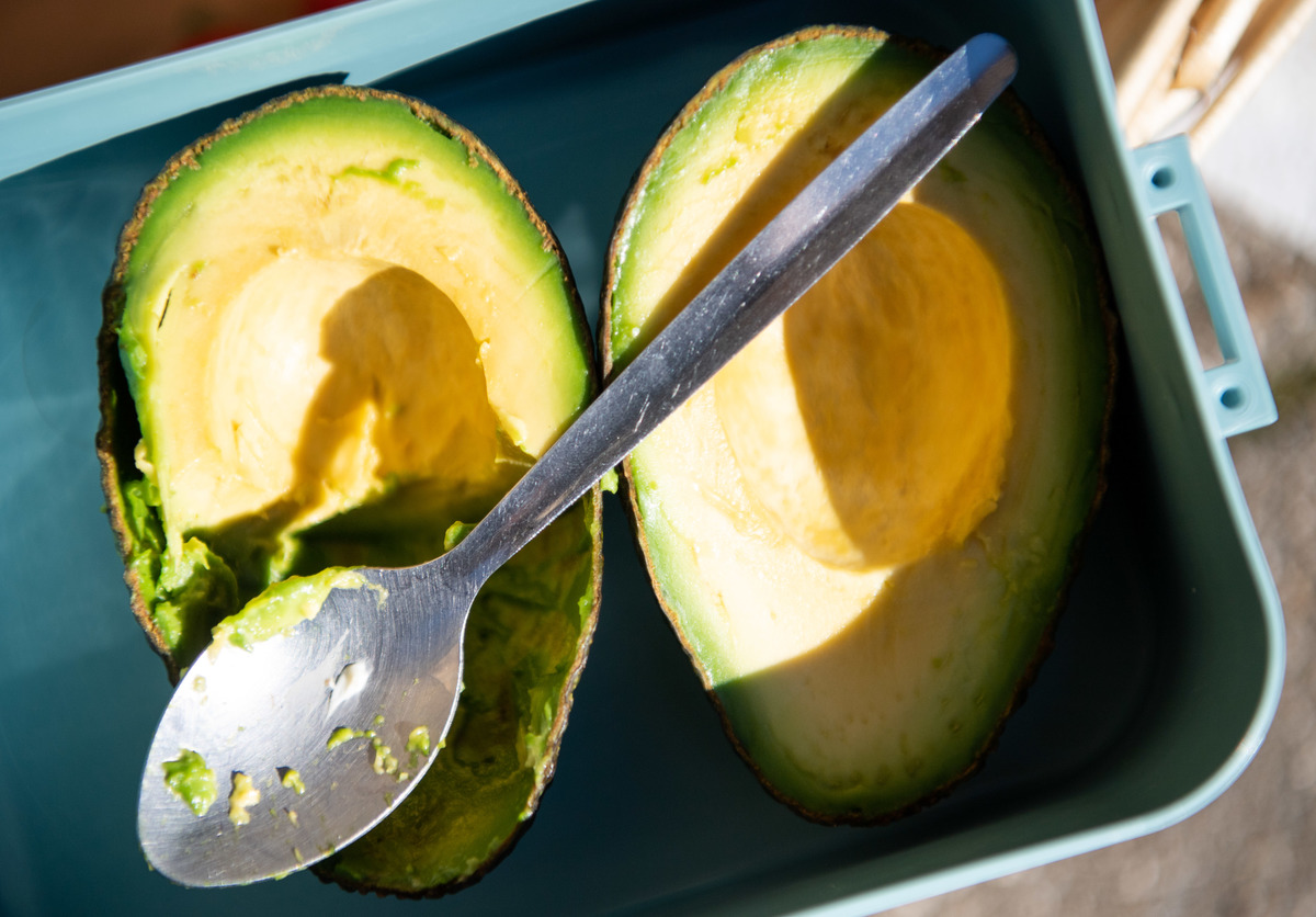 A spoon lies over a sliced avocado.
