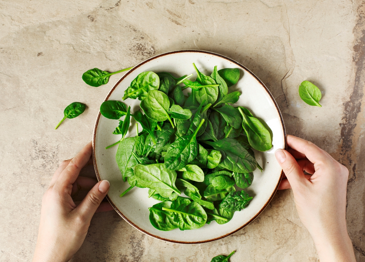 Woman's hands holding a plate with fresh spinach, top view