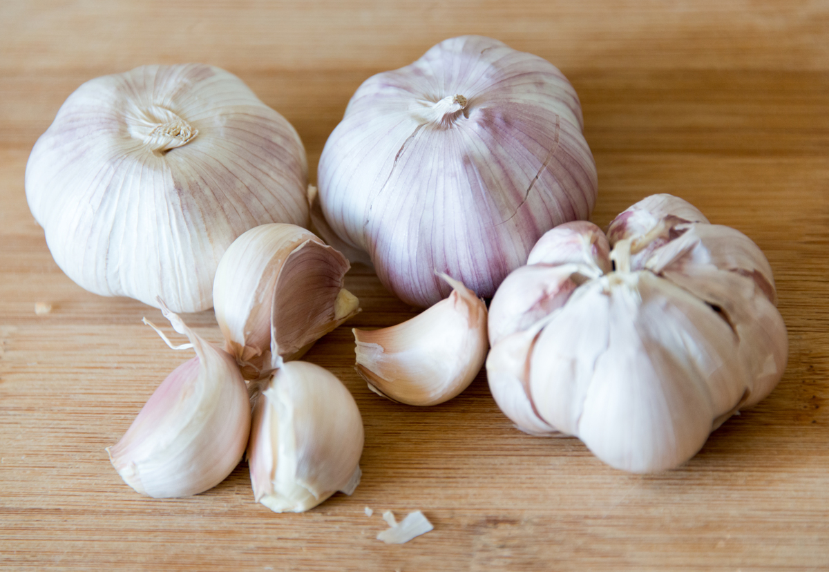 Garlic cloves sits on a wooden cutting board