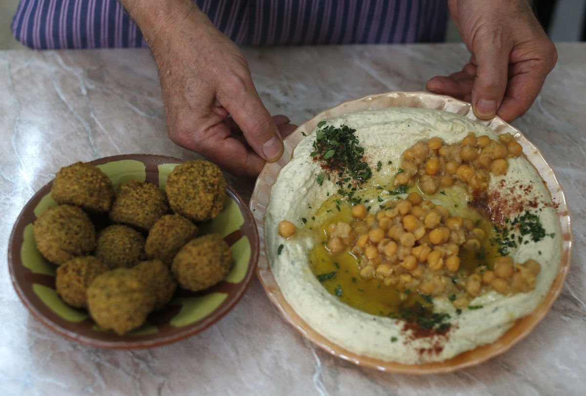 Palestinian restaurant owner Yasser Taha displays a plate of hummus, a paste made from chickpeas, and a bowel of falafel which are made from mashed and fried chickpeas