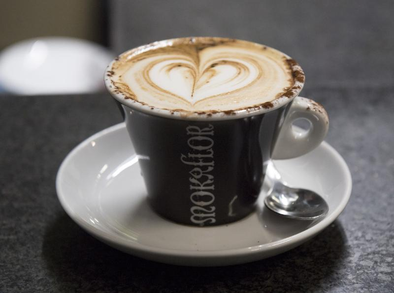 A coffee with foam in the shape of a heart