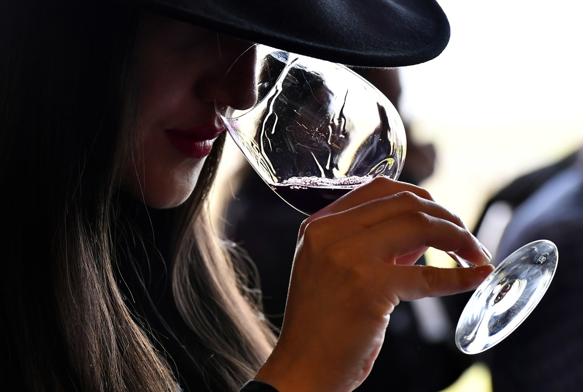 A woman tastes red wine during a wine tasting session at the Chateau La Dominique in Saint-Emilion