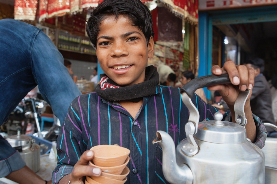 A smiling boy serving chai tea in India