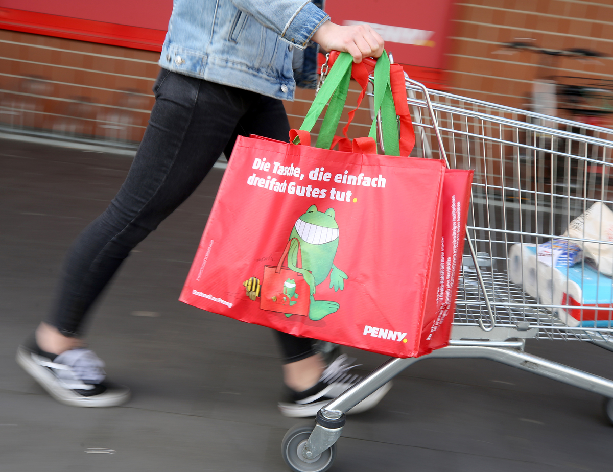 A woman leaves a supermarket with a reusable shopping bag in Duisburg, Germany