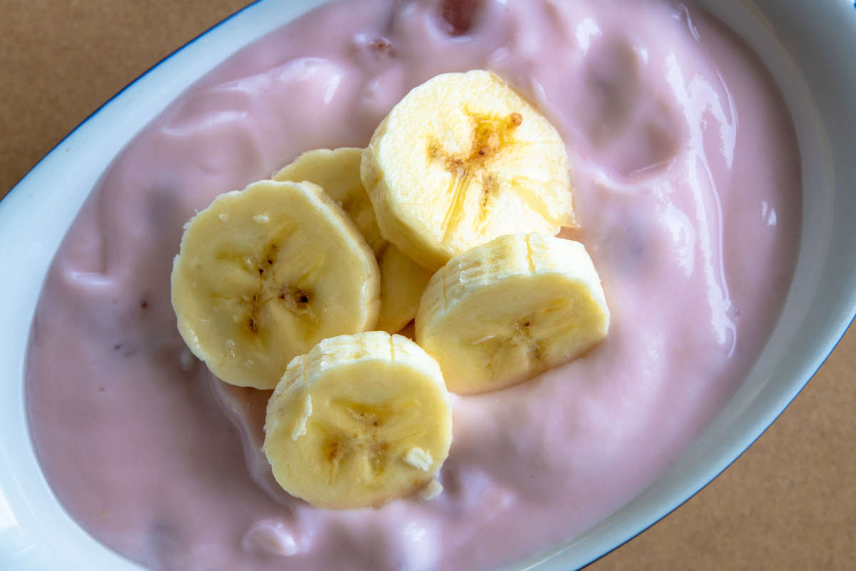 strawberry yogurt with pieces of ripe banana on top.