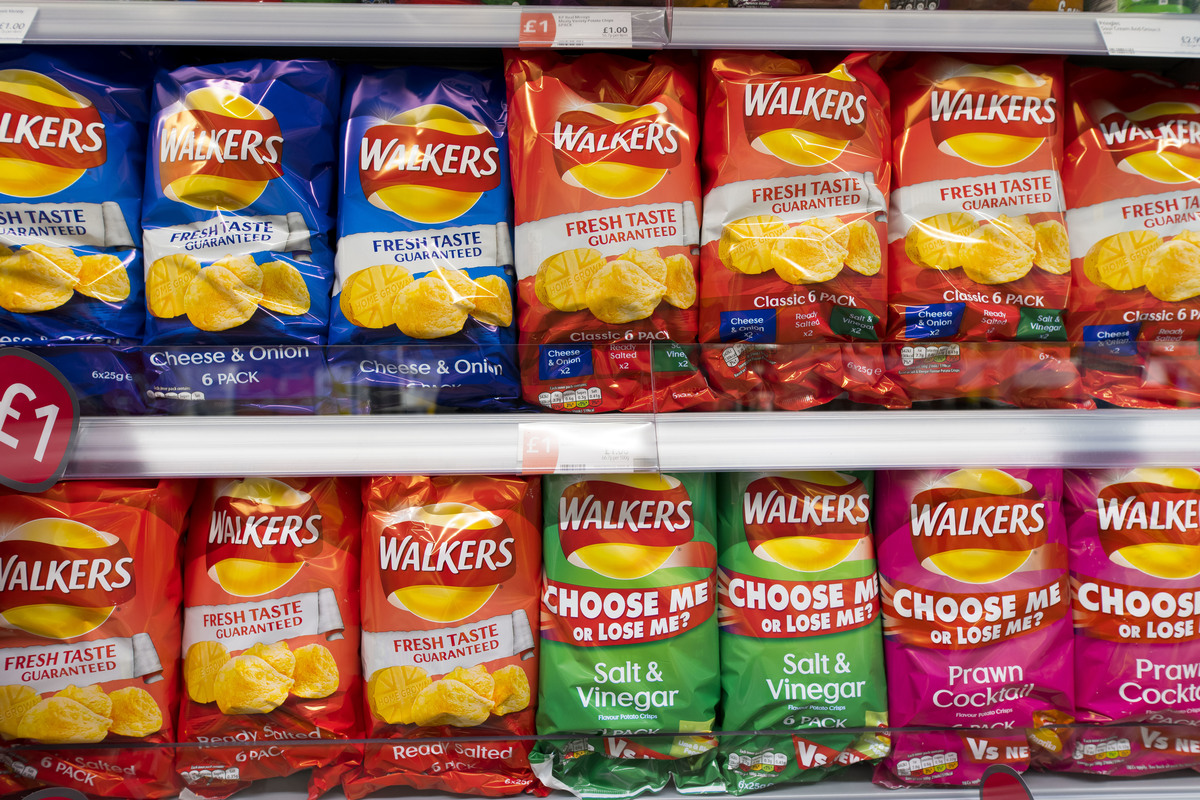 Multiple bags of Walkers crisps in different colors on display in a supermarket