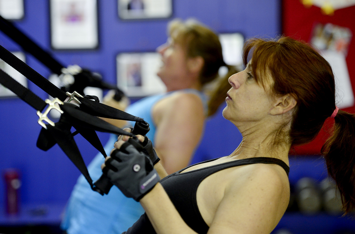 Sharon Montini does trx rows during a workout Wednesday morning, Oct. 01, 2014 at Fit Chick Express, 1254 Sherman Dr., Longmont.