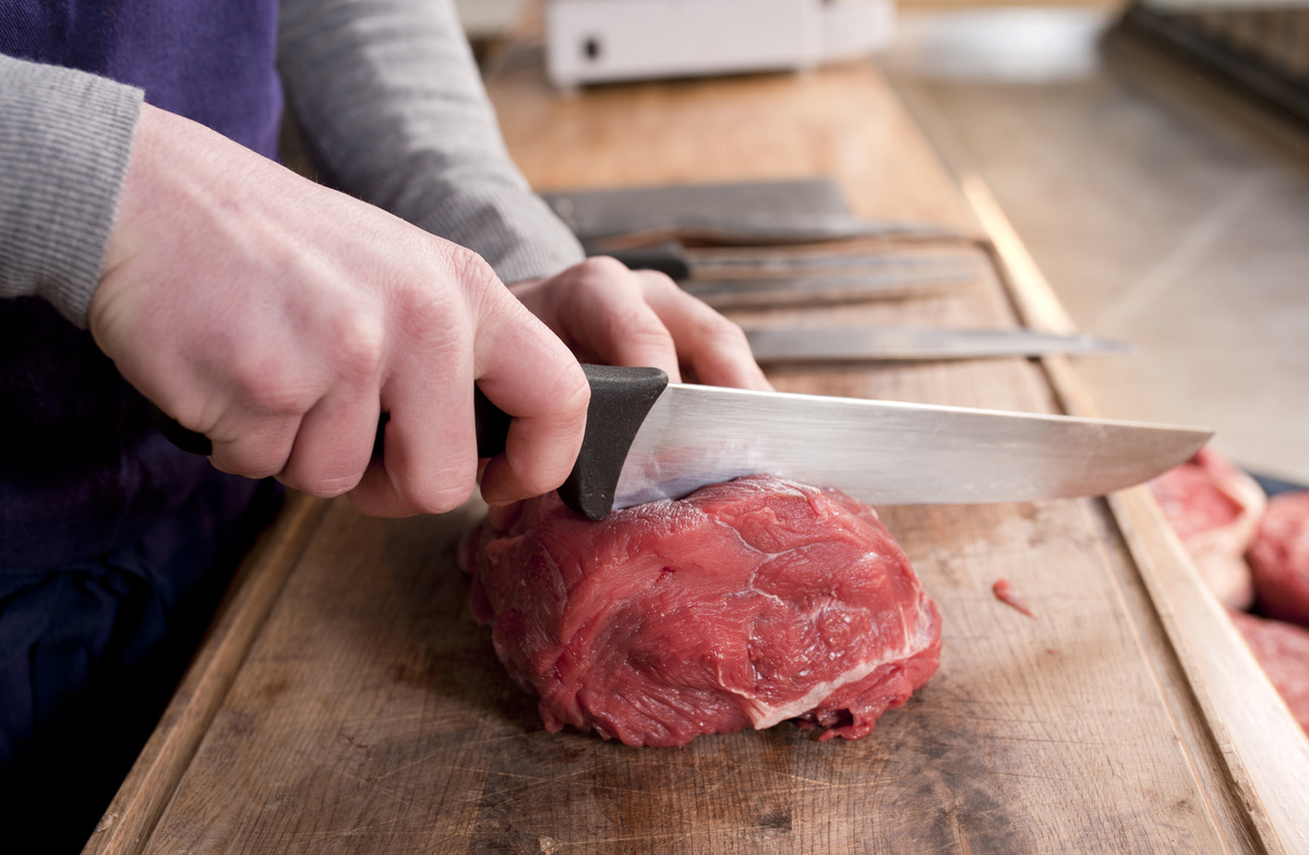 Close up shot of the hands of a butcher cutting a piece of meat.