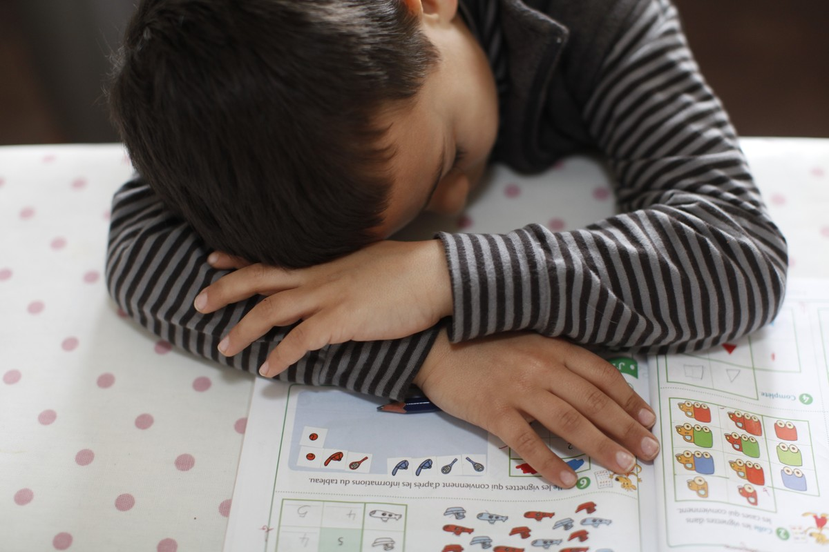 6-year-old boy falling asleep on his homework, France.