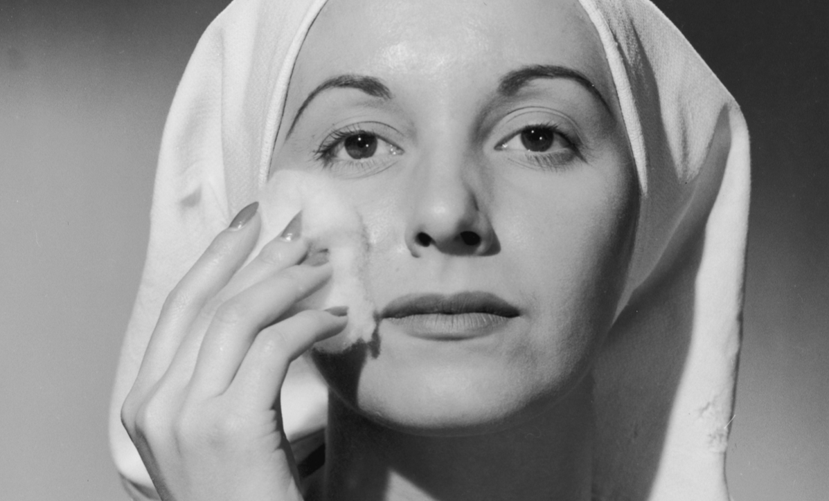 A headshot of a woman removing her makeup with a cotton ball, circa 1945.