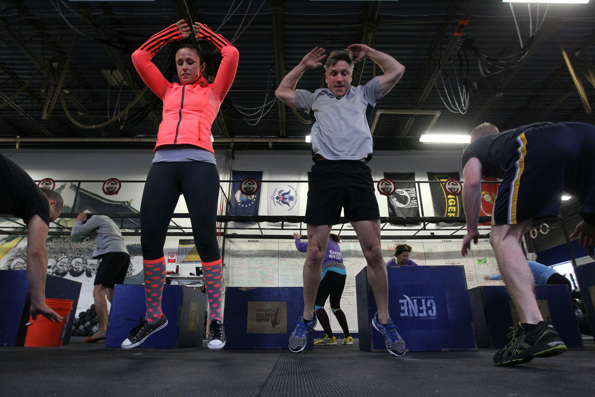 Maureen Becker and Dan Dougherty, both of Natick, jump high as they do burpees during a warm-up in a class at Crossfit New England.