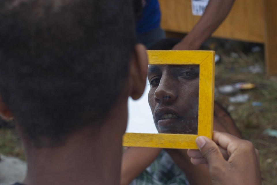 A Rohingya man checks his face in the mirror after getting a shave