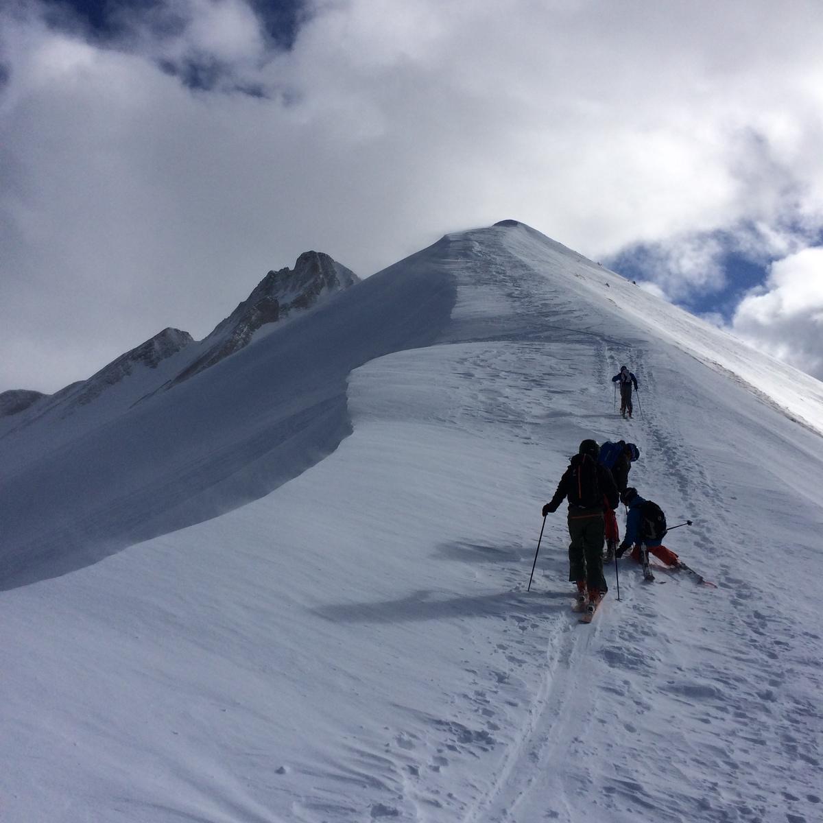 people skinning up to a mountain peak