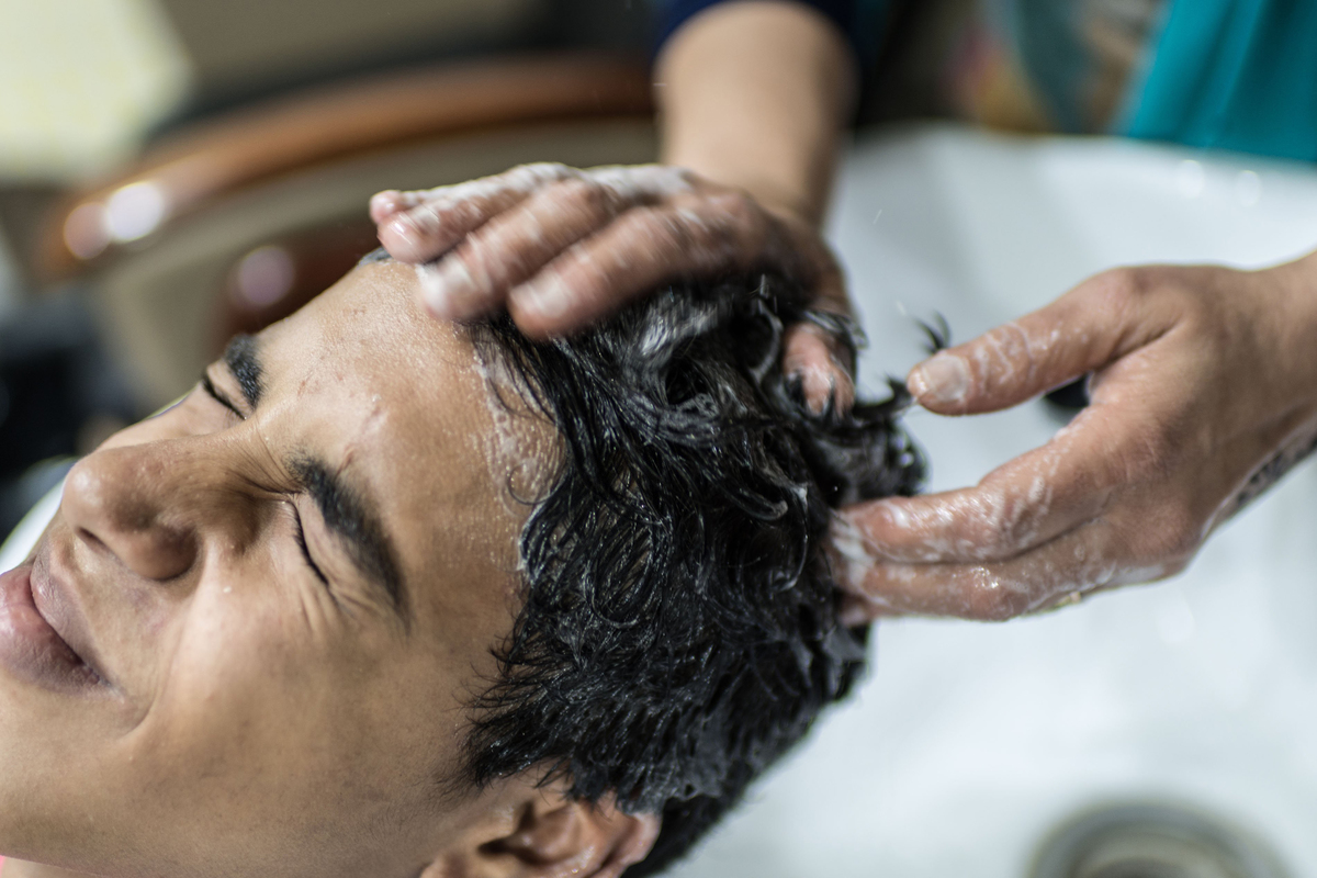 an Egyptian female barber, washes hair for a man at the barbershop she owns in the Nasr City of Cairo, Egypt