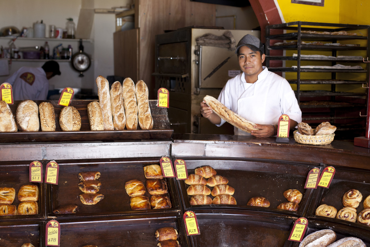 Young Mexican man in a bakery showing the bread he has for sale