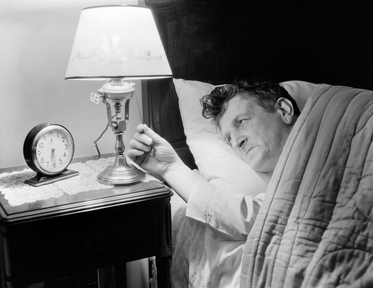 1940s TIRED MAN IN BED TURNING ON LIGHT NEXT TO ALARM CLOCK