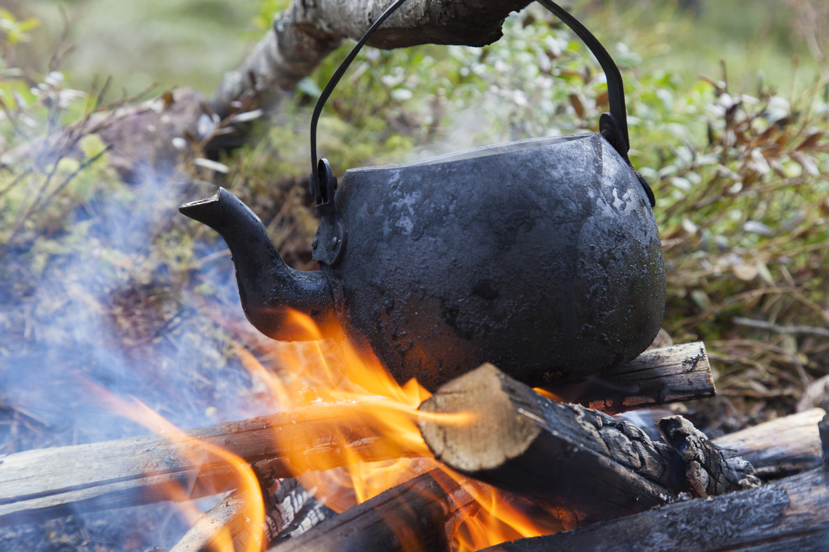 Blackened tin kettle boiling water over flames from campfire during hike.