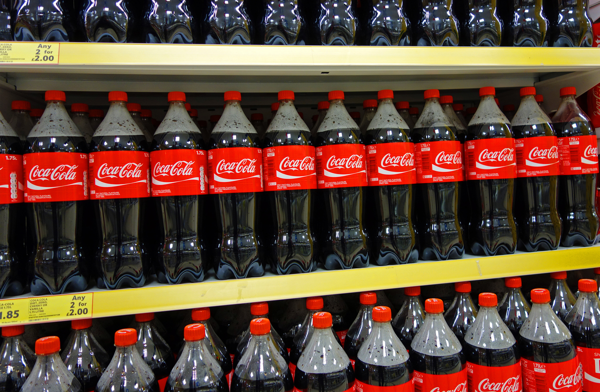 bottles of coca cola on shelves in a store in England, UK