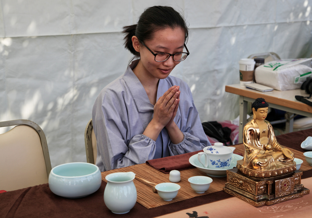 Chinese Buddhist woman participates in a traditional tea ceremony