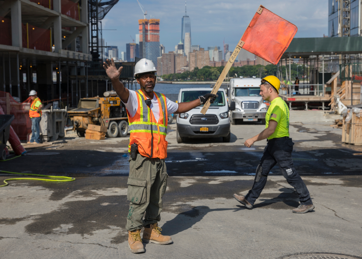 An employee of a construction company stops traffic at the site of a new apartment complex in New York