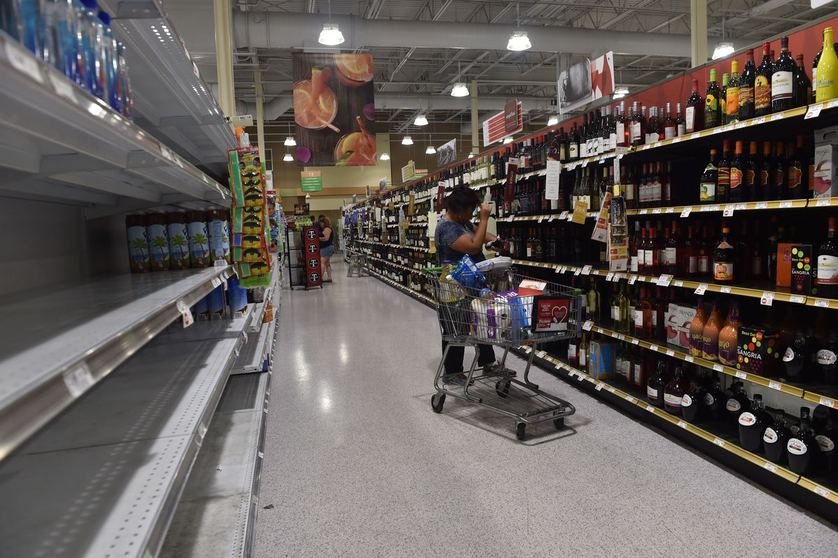A woman buys wine across from the empty water shelf in a supermarket in Riverview, Florida