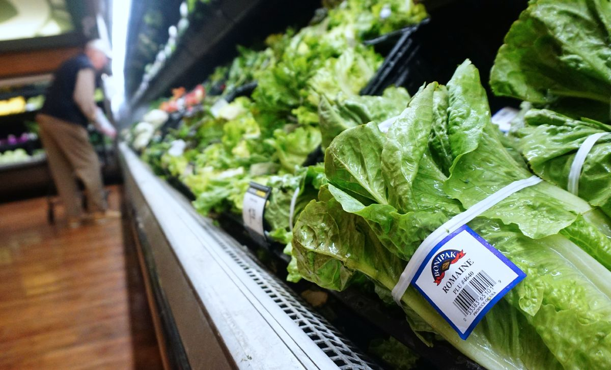 A man shops for vegetables beside Romaine lettuce stocked and for sale at a supermarket in Los Angeles