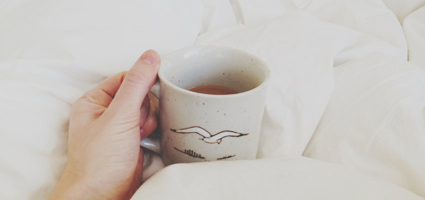 Person drinking tea in bed filled with white sheets.