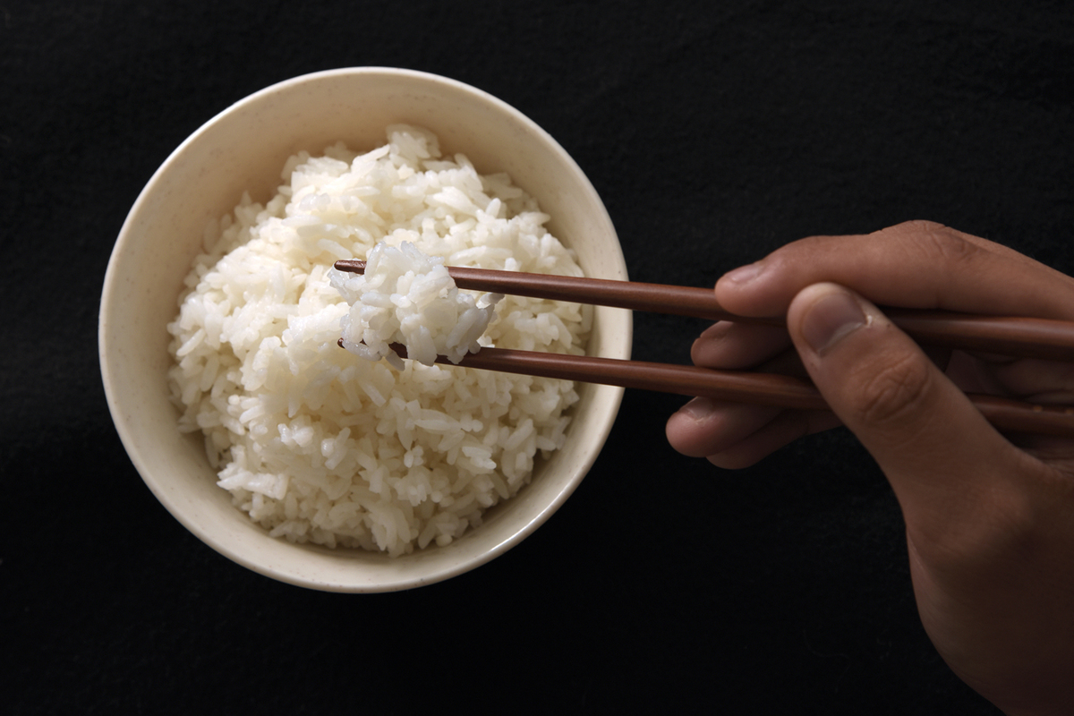 white rice in bowl being eaten with chopsticks