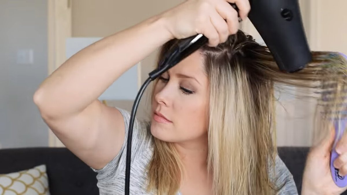 a woman blow dries her hair