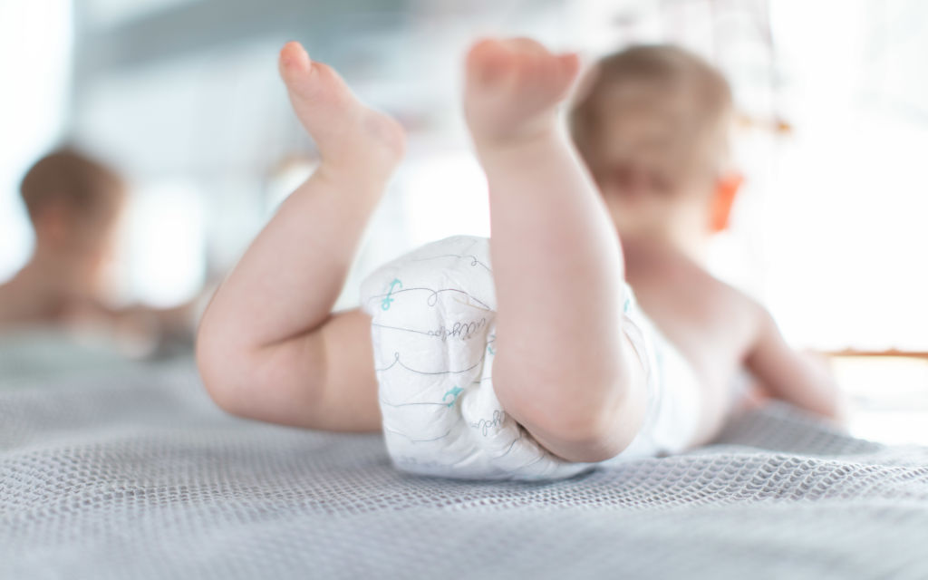 An infant wears Pampers while lying on a chest of drawers