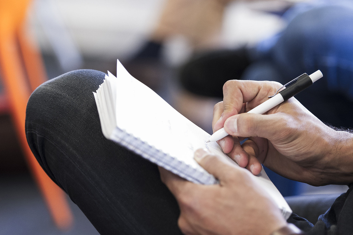 Note-taking on a pice of sheet with a pen during a business meeting
