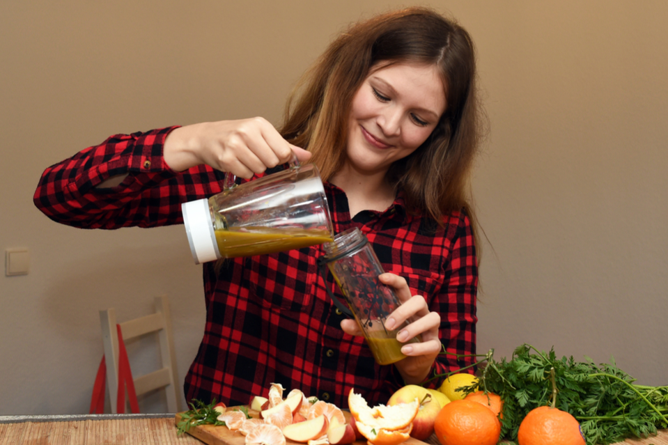 A young woman pours a freshly prepared smoothie, made from fresh fruit and vegetables, into a drinking bottle