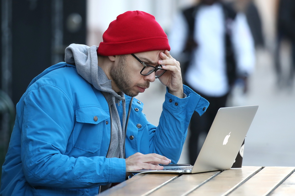 A man using his laptop in a sidewalk cafe in Moscow, Russia