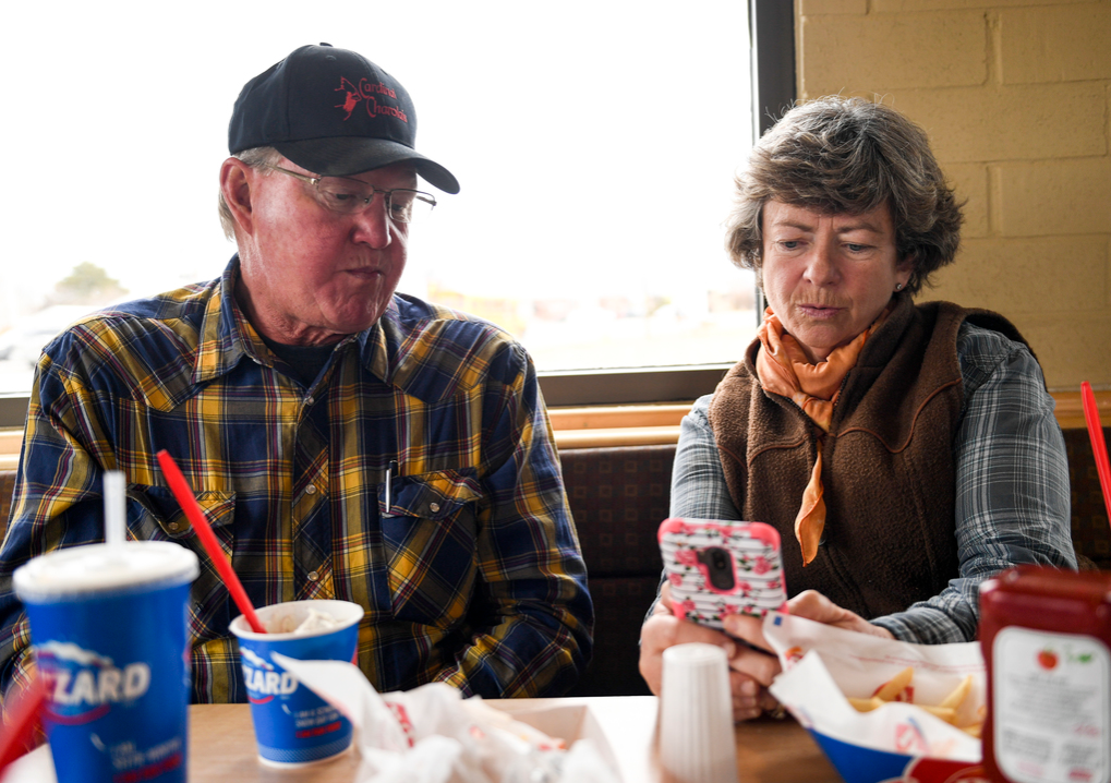 Howard and Janie VanWinkle look at the precipitation report on Janie's phone as they eat Blizzards at Dairy Queen