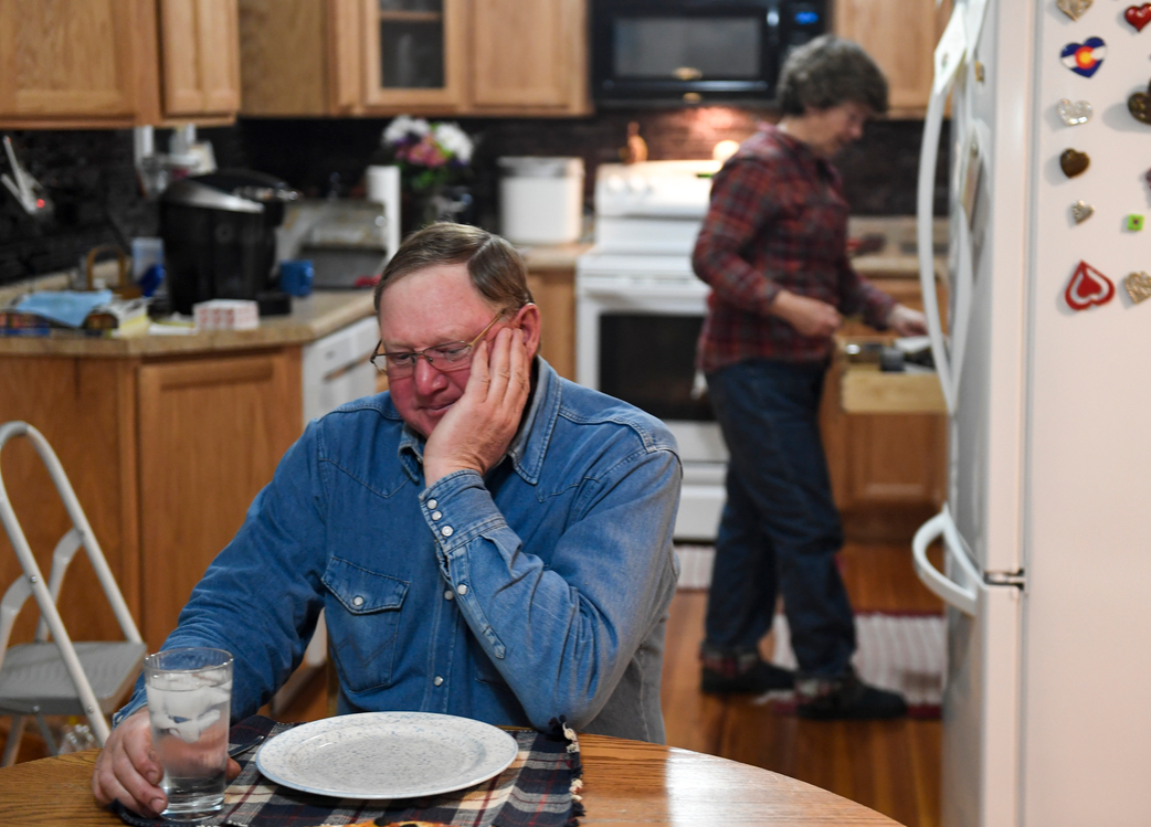 Howard VanWinkle rests his face on his hand as he prepares to eat dinner at nearly 9:30 p.m.