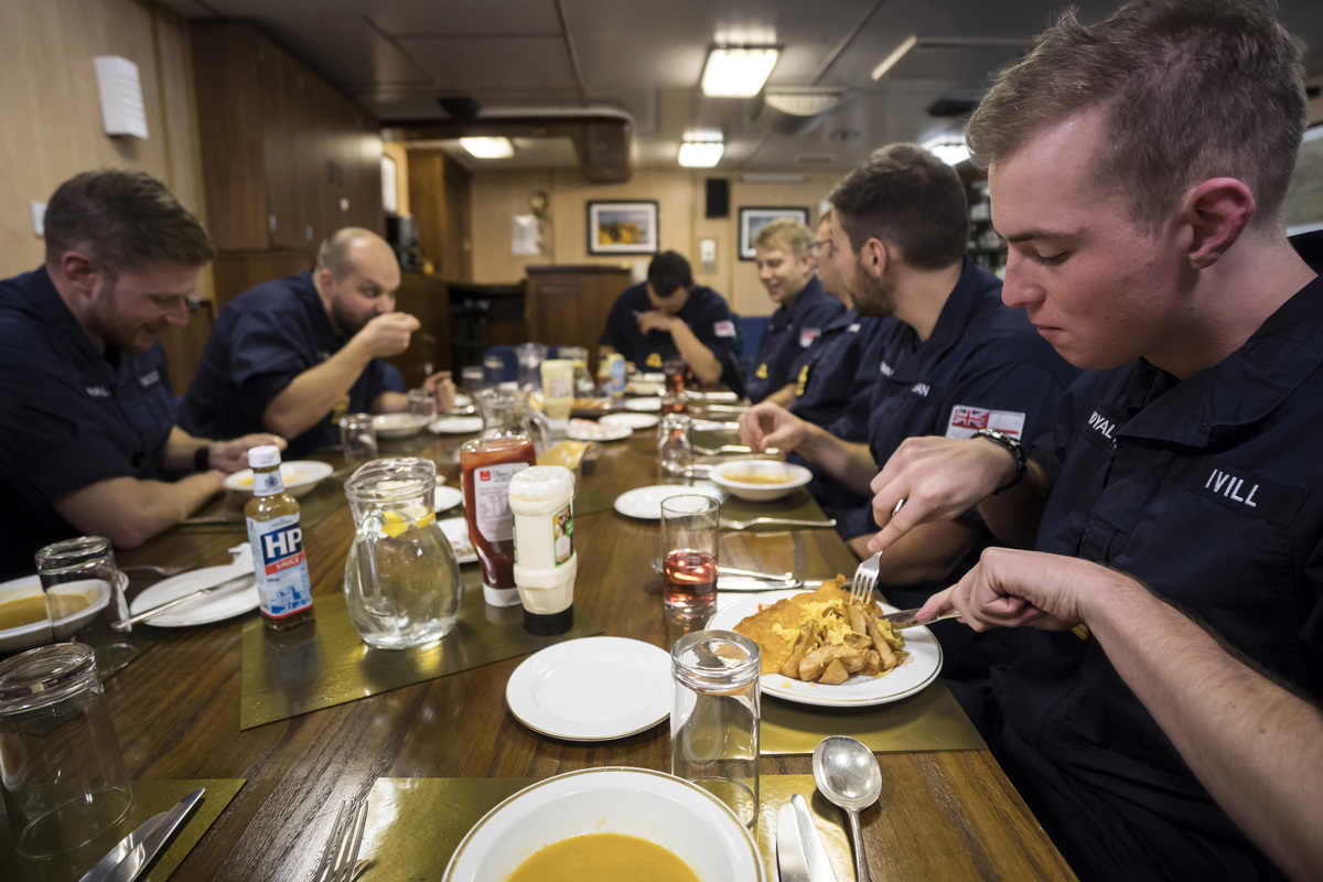 Members of the British Royal Navy eat lunch on board the HMS Montrose frigate