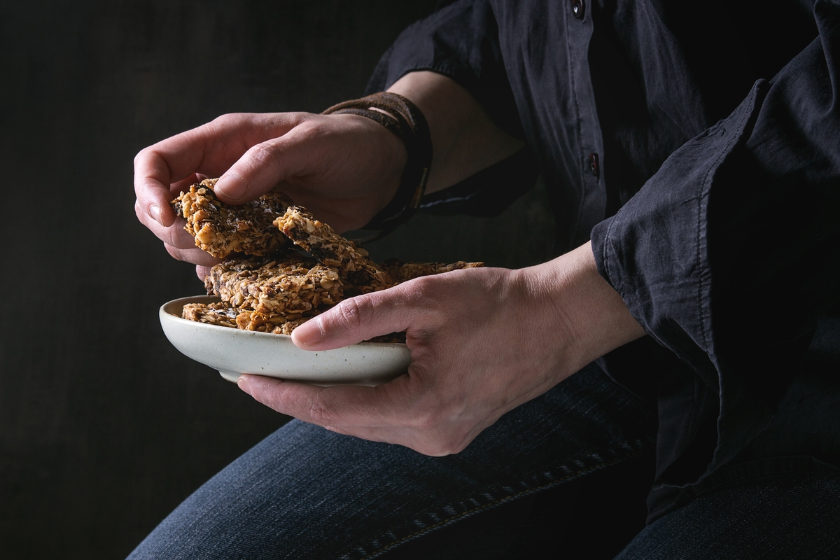 Woman in black shirt holding ceramic plate with homemade energy oats granola bars with dried fruits and nuts over black background.